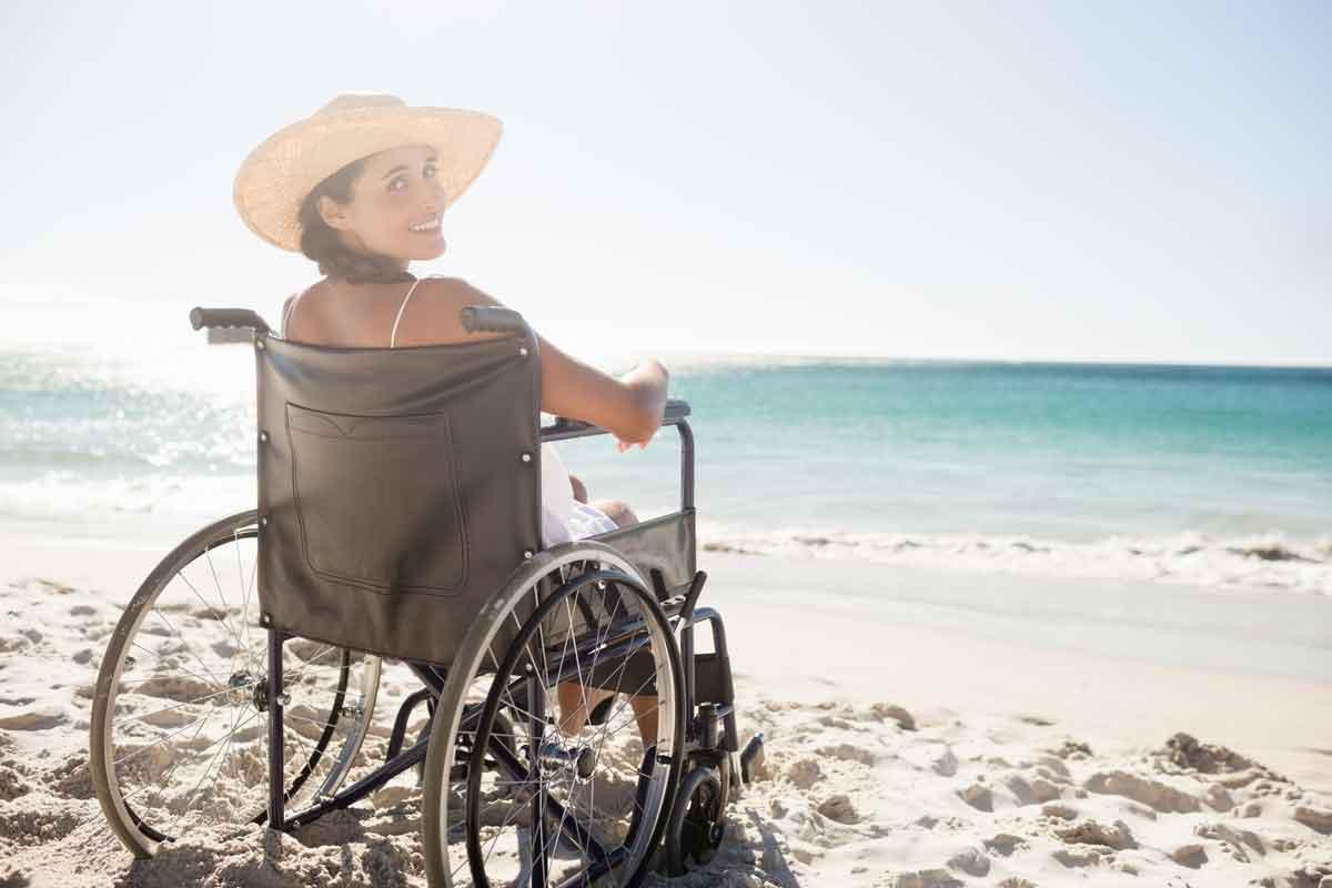 vrouw in rolstoel op het strand in Zeeland